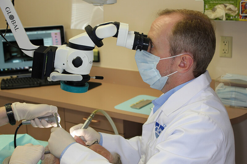 Dentist looking into microsope